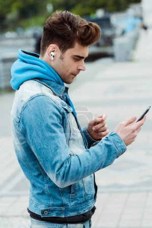 Photo for Side view of handsome young man using earphones and smartphone on urban street - Royalty Free Image