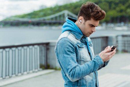 Photo pour Jeune homme utilisant des écouteurs et un téléphone portable dans la rue urbaine - image libre de droit