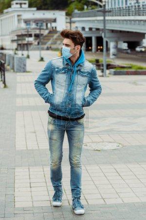 Photo pour Jeune homme en masque médical et les mains dans des poches de veste en denim marchant sur la rue urbaine - image libre de droit