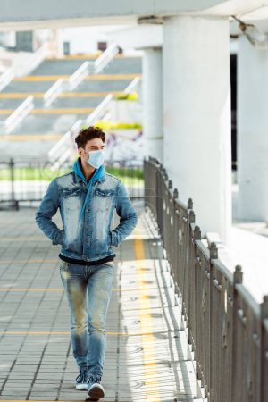 Young man in medical mask with hands in pockets of jacket walking on urban street