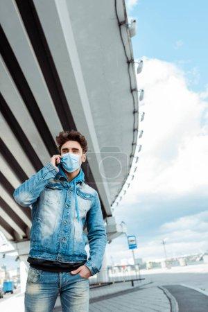 Photo pour Homme en masque médical parlant sur téléphone portable avec pont et ciel nuageux à l'arrière-plan - image libre de droit