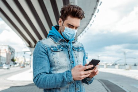 Photo for Young man in medical mask using smartphone on city street - Royalty Free Image