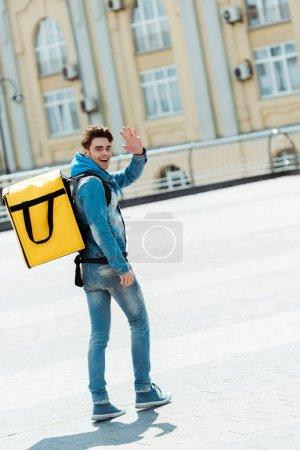 Photo pour Vue arrière du messager heureux avec sac à dos thermique agitant la main à la caméra sur la rue de la ville - image libre de droit