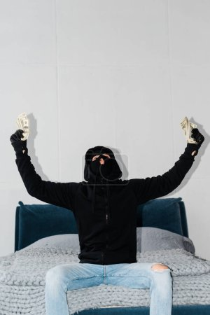 Photo for Robber in balaclava and leather gloves holding dollars on bed - Royalty Free Image