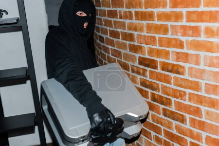 Photo for Thief in leather glove and balaclava holding wireless speaker during stealing - Royalty Free Image
