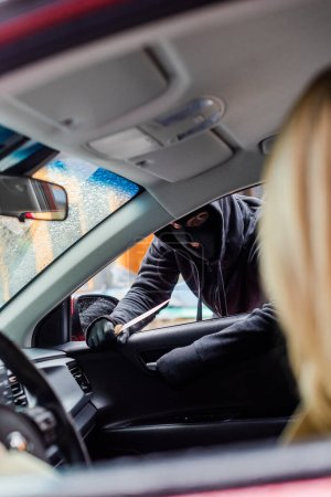 Photo for Selective focus of robber in balaclava holding knife and opening car door near driver - Royalty Free Image