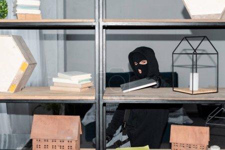 Photo pour Voleur en masque et gants en cuir prenant ordinateur portable de placard pendant le vol - image libre de droit
