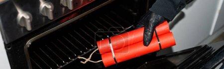 Photo pour Vue panoramique du voleur en gant de cuir mettant de la dynamite dans le poêle dans la cuisine - image libre de droit