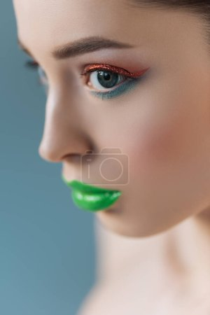 Photo for Portrait of beautiful woman with green lips, pink and blue eyeshadow isolated on blue, selective focus - Royalty Free Image