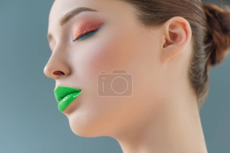 Photo for Portrait of beautiful woman with green lips, pink and blue eyeshadow and closed eyes isolated on blue - Royalty Free Image