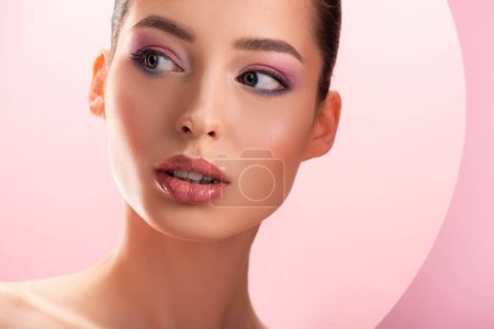 Photo for Portrait of beautiful naked woman with shiny makeup looking away through round paper hole isolated on pink - Royalty Free Image
