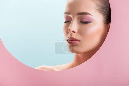 Photo pour Portrait de belle femme nue avec maquillage brillant dans un trou de papier rond avec les yeux fermés isolé sur bleu - image libre de droit
