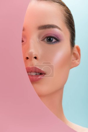 Photo for Portrait of beautiful woman with shiny makeup looking through round paper hole isolated on blue - Royalty Free Image