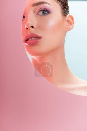 Foto de Retrato de hermosa mujer desnuda con maquillaje brillante mirando a través de un agujero de papel redondo aislado en azul. - Imagen libre de derechos