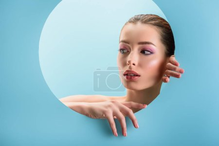 Photo for Portrait of beautiful naked woman with glossy lips, pink eyeshadow looking through paper round hole isolated on blue - Royalty Free Image