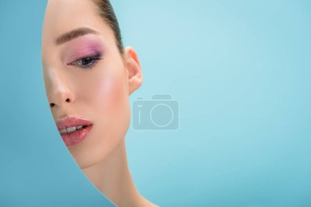 portrait of beautiful woman with glossy lips, pink eyeshadow behind paper round hole isolated on blue