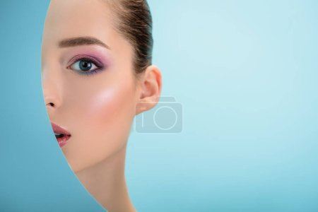 Photo for Portrait of beautiful woman with glossy lips, pink eyeshadow behind paper round hole isolated on blue - Royalty Free Image