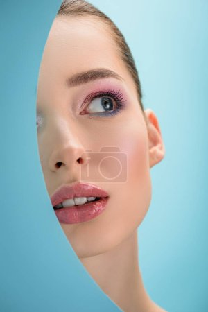 Photo for Portrait of beautiful young woman with glossy lips, pink eyeshadow looking up through paper round hole isolated on blue - Royalty Free Image