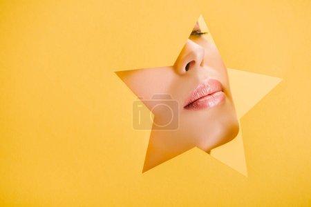 Foto de Vista recortada de la hermosa mujer con labios brillantes en el agujero en forma de estrella de papel aislado en amarillo - Imagen libre de derechos