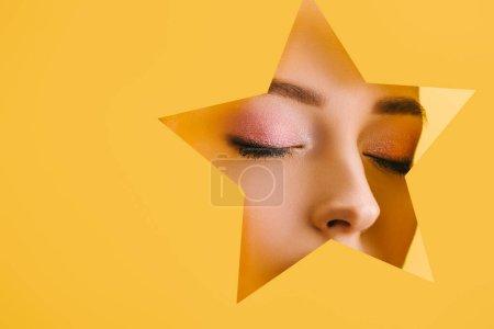 Photo pour Portrait de belle femme avec un maquillage brillant en papier trou en forme d'étoile avec les yeux fermés isolé sur jaune - image libre de droit