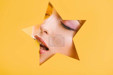 Photo pour Portrait de belle femme avec un maquillage brillant en papier trou en forme d'étoile avec les yeux fermés et bouche ouverte isolé sur jaune - image libre de droit