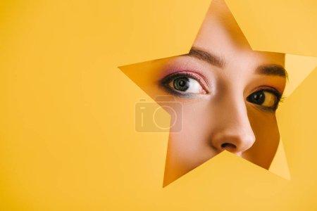 Foto de Retrato de mujer hermosa con maquillaje brillante en el agujero en forma de estrella de papel mirando a la cámara aislada en amarillo - Imagen libre de derechos