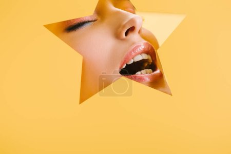 Foto de Retrato de mujer hermosa con maquillaje brillante en el agujero en forma de estrella de papel con los ojos cerrados y la boca abierta aislada en amarillo - Imagen libre de derechos