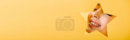 Foto de Retrato de mujer hermosa con maquillaje brillante en el agujero en forma de estrella de papel sonriendo aislado en amarillo, tiro panorámico - Imagen libre de derechos