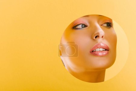 Photo for Portrait of beautiful woman with shiny makeup in paper round hole looking away isolated on yellow - Royalty Free Image