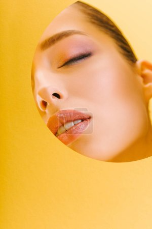 Photo for Portrait of beautiful woman with shiny makeup in paper round hole with closed eyes isolated on yellow - Royalty Free Image