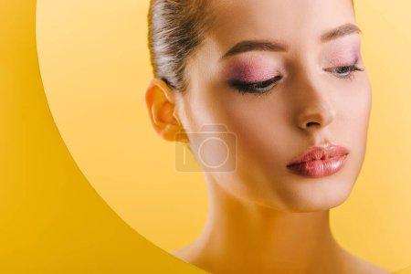 Photo pour Portrait de belle femme avec maquillage brillant dans un trou rond en papier regardant vers le bas isolé sur jaune - image libre de droit