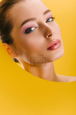 Photo for Portrait of beautiful woman with shiny makeup in paper round hole looking at camera isolated on yellow - Royalty Free Image