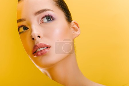 Photo for Portrait of beautiful woman with shiny makeup in paper round hole looking up isolated on yellow - Royalty Free Image