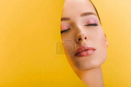 Photo pour Portrait de belle femme avec un maquillage brillant dans un trou rond en papier avec les yeux fermés isolé sur jaune - image libre de droit