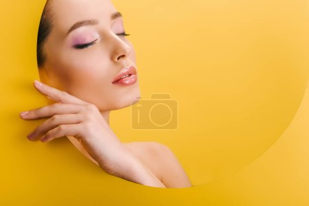 Photo for Portrait of beautiful naked woman with shiny makeup in paper round hole with hand and closed eyes isolated on yellow - Royalty Free Image