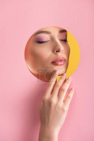 Photo pour Portrait de belle femme avec maquillage brillant en papier rose trou rond avec la main et les yeux fermés isolé sur jaune - image libre de droit