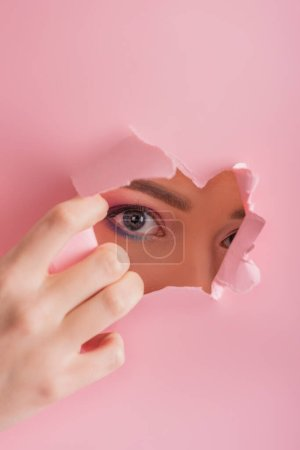 Photo for Beautiful woman with shiny makeup looking through paper torn hole isolated on pink - Royalty Free Image