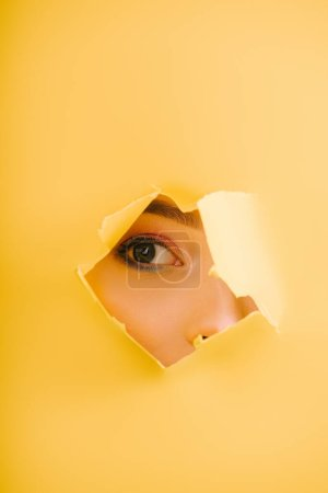 Photo for Cropped view of beautiful woman looking through yellow paper torn hole - Royalty Free Image