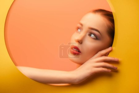 Photo for Blurred image of beautiful woman in yellow paper circle hole looking away - Royalty Free Image