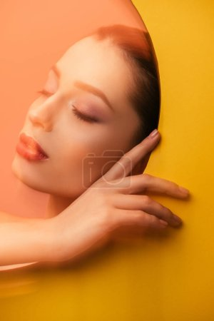 Photo for Blurred image of beautiful woman with closed eyes in yellow paper circle hole - Royalty Free Image