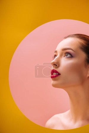 Photo for Naked beautiful woman with crimson lips looking away through yellow paper circle hole - Royalty Free Image