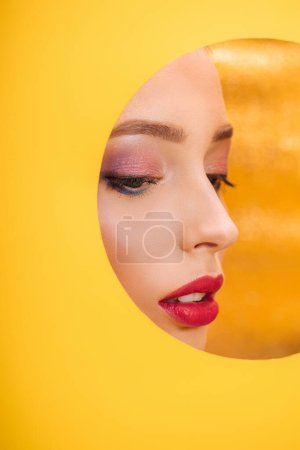 Photo for Beautiful woman with colorful makeup looking through yellow paper circle hole - Royalty Free Image