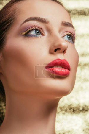 Photo for Portrait of beautiful woman with shiny makeup looking away on golden background - Royalty Free Image