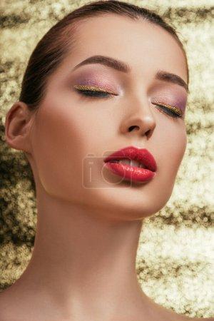 Foto de Retrato de mujer hermosa con maquillaje brillante y ojos cerrados sobre fondo dorado - Imagen libre de derechos
