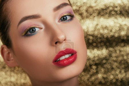 Photo for Portrait of beautiful woman with shiny makeup on golden background - Royalty Free Image