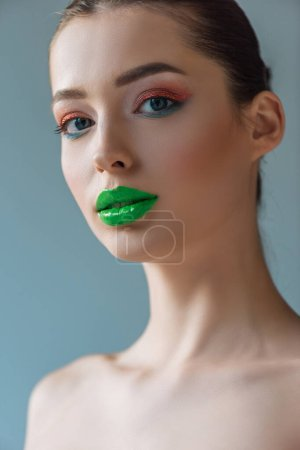 Photo for Portrait of beautiful naked woman with green lips, pink and blue eyeshadow isolated on blue - Royalty Free Image