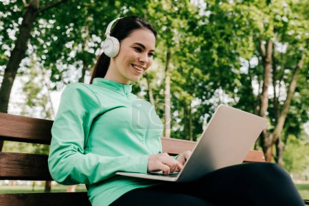 Photo for Smiling girl in headphones using laptop on bench in park - Royalty Free Image