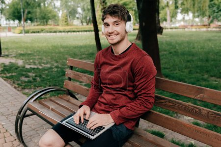 Smiling man in headphones looking at camera while using laptop in park