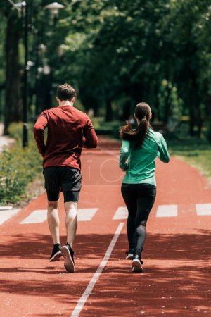 Photo for Back view of couple running on running path in park - Royalty Free Image