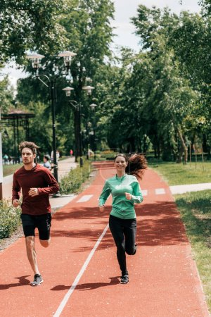 Photo for Handsome man running near positive girlfriend on running path in park - Royalty Free Image